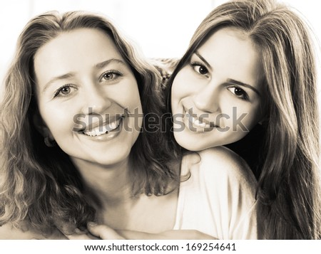 Black and white close up portrait of a mother and teen daughter being close and hugging at home being happy and joyful  - stock photo