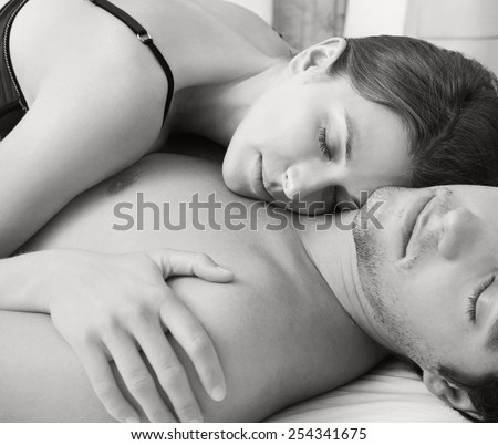 Black and white close up portrait of an attractive young couple sleeping together while hugging on a bed, indoors. Couple and romance living lifestyle. Sensuality and relationships, home interior. - stock photo