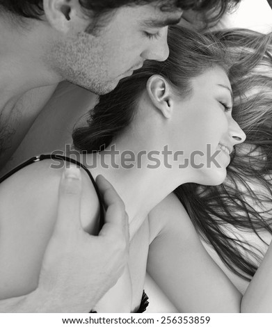 Black and white close up portrait of attractive young lovers couple together in bed with man kissing woman on neck, wearing sexy lingerie in a hotel room, interior. Romance and sex lifestyle indoors. - stock photo