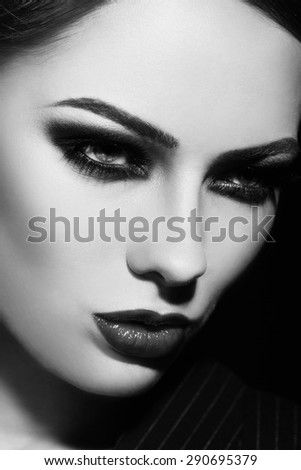 Black and white close-up portrait of young beautiful woman with smoky eyes - stock photo
