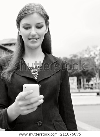 Black and white close up portrait view of an attractive smiling young professional businesswoman using smartphone technology in a classic city, outdoors. (Business, People, Technology) - stock photo