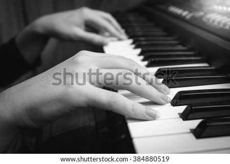 Black and white closeup photo of female hands on digital piano keyboard - stock photo