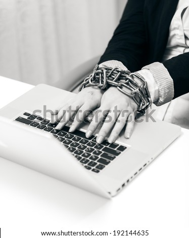 Black and white closeup photo of woman locked to laptop by chain - stock photo