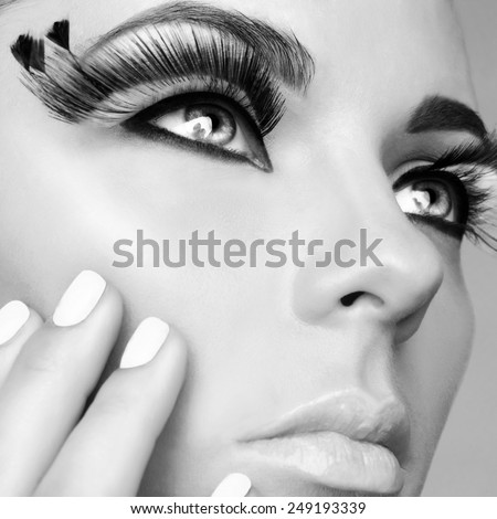 Black and white closeup portrait of lady with beautiful eyelashes. Makeup and manicure - stock photo