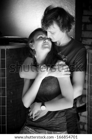Black and white closeup portrait of man hugging his girlfriend from back on street
