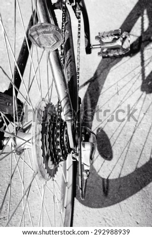 Black and white Cogwheel on a bicycle against shadow - stock photo