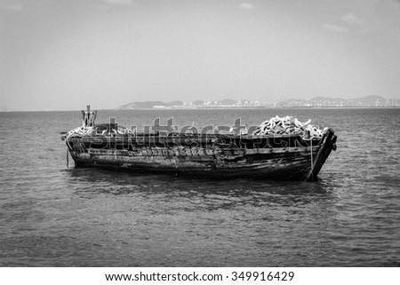 Black and white color of old fishing boats in sea. - stock photo