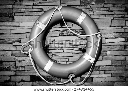 Black and white color of Ring buoy on the stonewall at the beach ready for emergency case - stock photo