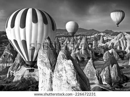Black-and-white contrast picture of the balloons flying over canyons with freakish rocks in Cappadocia. - stock photo
