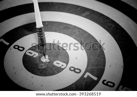 Black and white - Dart is an opportunity and Dartboard is the target and goal. So both of that represent a challenge. Bullseye and Dart. opportunity, risk management, business concept.