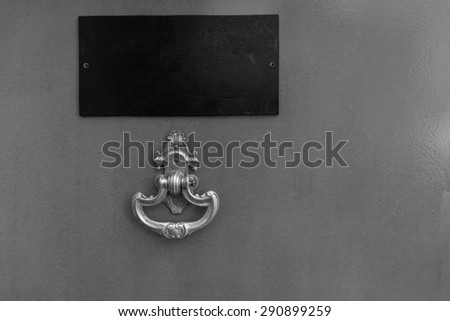 Black and White Detail of Door with Ornate Knocker and Blank Name Plate and Copy Space - stock photo