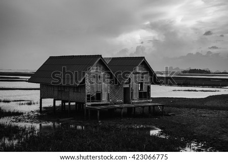 Black and white dilapidated of house in lagoon at Talaynoi, Phat