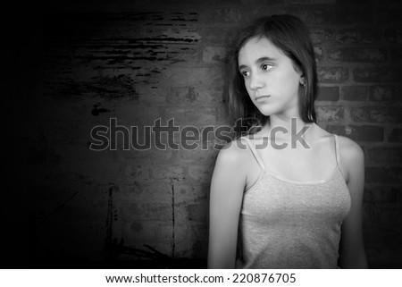 Black and white dramatic portrait of a sad teenage girl leaning on a grunge brick wall with space for text - stock photo