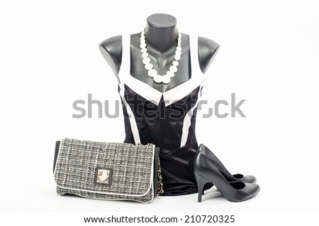 Black and white dress on mannequin with matching accessories. Elegant dress on tailor's dummy with matching purse,high heels and necklace - stock photo