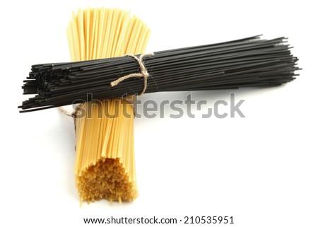 Black and white dry spaghetti isolated on white background - stock photo
