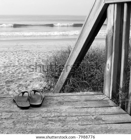 Black and white DSLR picture of leather strap sandals on a boardwalk with steps to the ocean, with sand and surf.  Copy space for text.