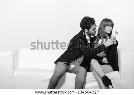 Black and white effect - girl smokes a cigar sitting on the couch while her boyfriend tries to take it from his hands