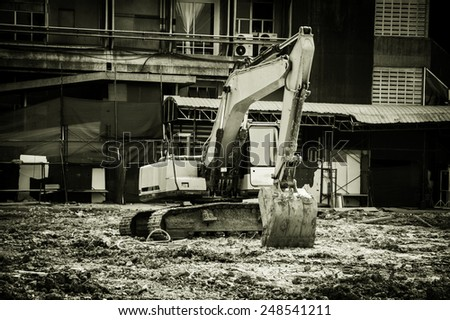 Black and white Excavator on construction site. - stock photo