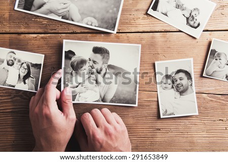 Black and white family photos laid on wooden floor background. - stock photo