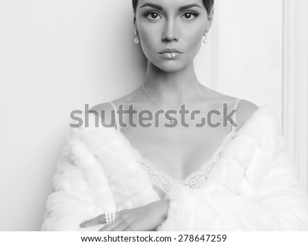 Black and white fashion photo of beautiful lady in elegant white fur coat - stock photo