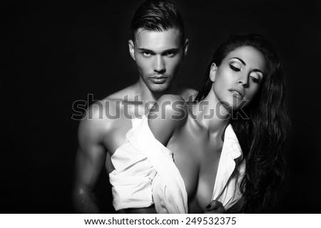 black and white fashion photo of sexy impassioned couple posing in studio    - stock photo