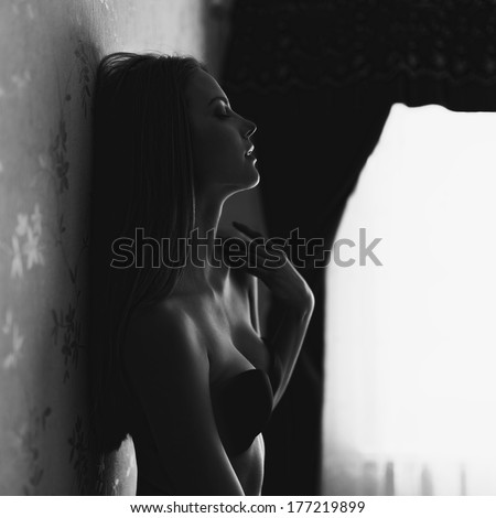 Black and white fashion portrait of a beautiful girl in lingerie near wall