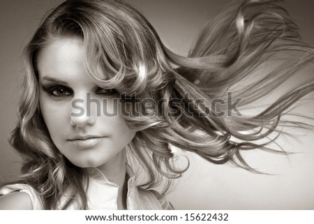 Black and white fashion portrait of a girl with hair lightly fluttering in the wind