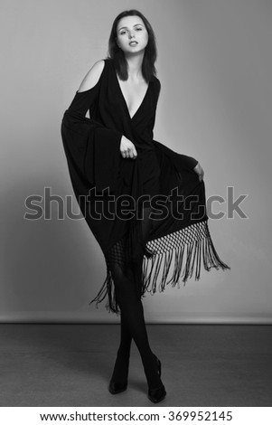 Black and white fashion portrait of slim young beautiful woman with white skin and dark hair in black flowing clothes standing on dark studio background