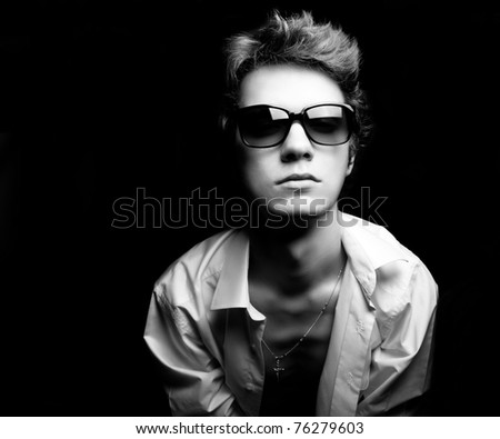 Black and white fashion portrait of the young guy dressed in shirt. Sunglasses - stock photo