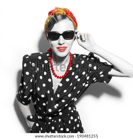 Black and white fashion portrait of woman in red scarf and sunglasses over white - stock photo