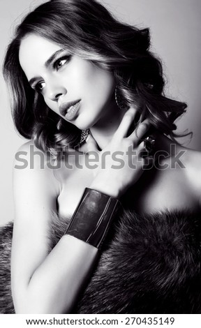 black and white fashion studio photo of beautiful sensual woman with dark hair in fur