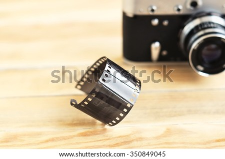 Black and white  film and vintage camera on a wooden table