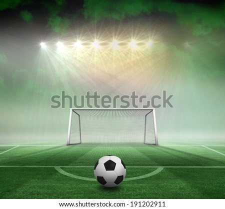 Black and white football against football pitch and goal under spotlights - stock photo