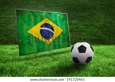 Black and white football on grass against brazil flag in grunge effect - stock photo