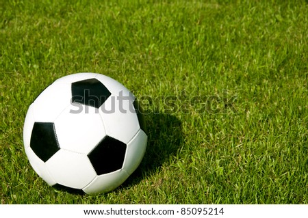 Black and white football on green grass