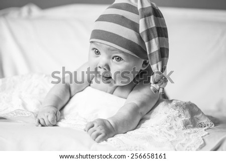 black and white, funny little girl lying on the bed and looking to the side, striped purple stocking on his head, like a gnome, stuck out her tongue, baby  - stock photo