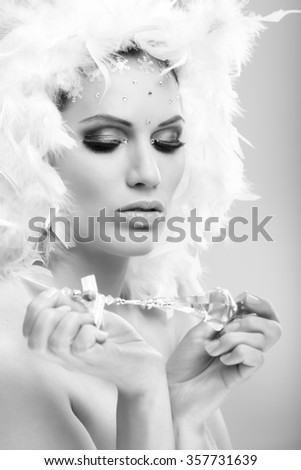 Black and white glamour photo of young winter beauty with professional makeup and crystal gem.