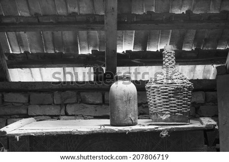Black and white glass, wooden and metallic objects in the attic with dust and spiderwebs in a beautiful, moody light. - stock photo