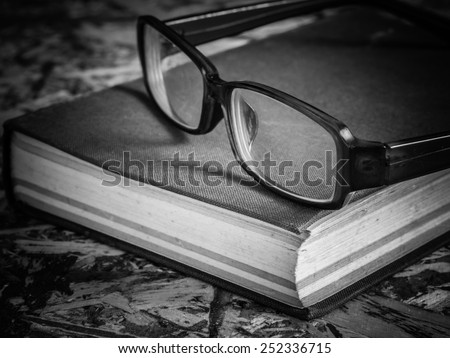 black and white glasses and book - stock photo