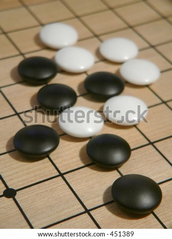 Black and White Go Pieces on Board - stock photo