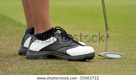 Black and white golf shoes with putter on green - stock photo