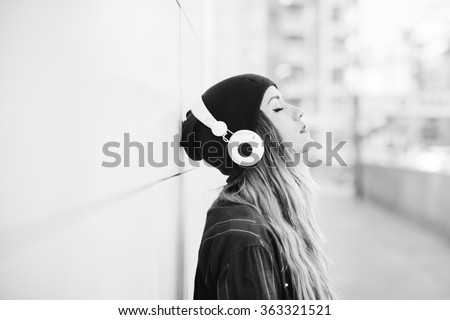 Black and white half length profile portrait of young handsome caucasian blonde hair woman leaning against a wall, listening music with headphones, eyes closed - serene, enjoying, music concept - stock photo