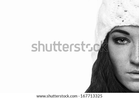 Black and white half portrait of brunette young woman in white warm hat. Isolated on white background. - stock photo