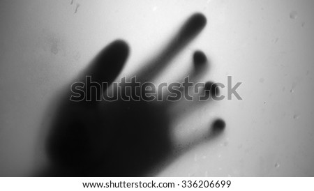 Black and White hand shadow through window glass. - stock photo