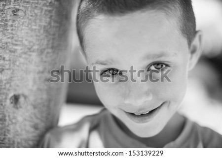 Black and white head shot of young boy smiling looking at camera leaning against a tree