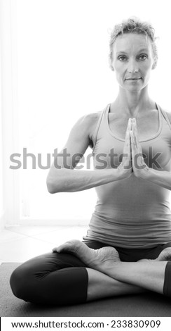 Black and white healthy and mature professional woman sitting in a yoga position with hands together, stretching and meditating against sunny glass doors, indoors. Exercising and well being. - stock photo