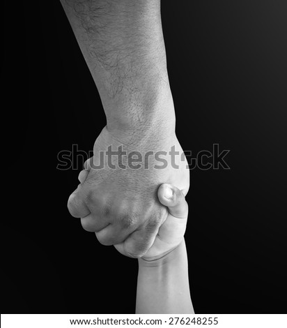 Black and white helping hand on black background. - stock photo