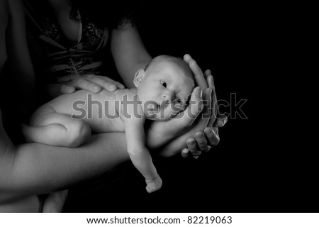 Black and White image of a baby being held by her parents. - stock photo