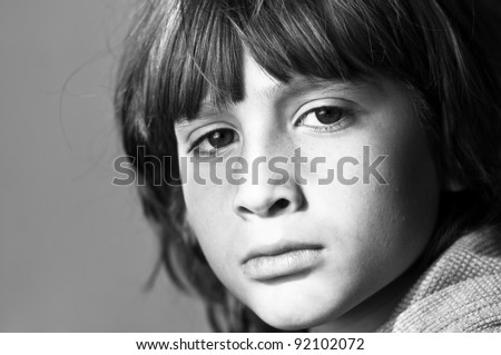Black and white image of a boy with his sad facial expression. Image signaling to stop violence against children. - stock photo