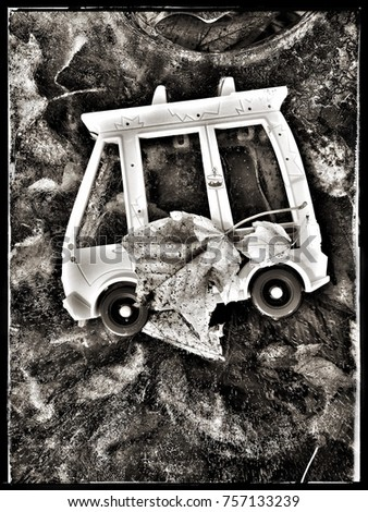 Black and white image of a car toy and fall leaves